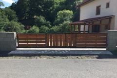 Motorizovaná brána s kovovým rámom a výplňou z dreva.